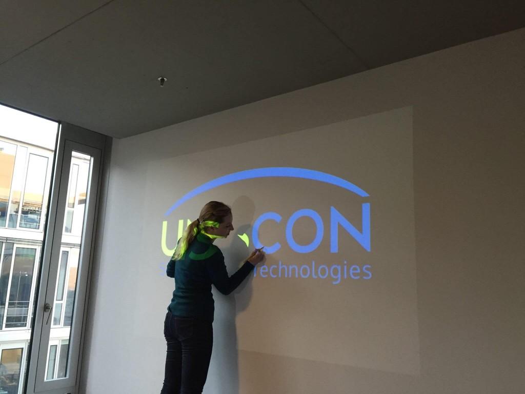 frau malt uniscon logo nach overhead vorlage